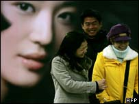 Chinese shoppers near billboard, AFP