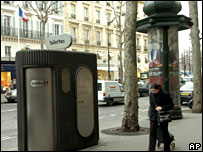 A woman walks past an automatic public toilet in Paris.