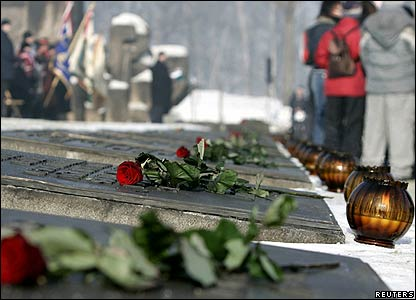Roses are placed on a monument during ceremony at the former death camp Auschwitz Birkena