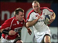 Matthew Rees of the Scarlets tries to stop Ulster's Andrew Maxwell