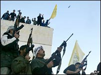 Fatah gunmen shoot in the air as they stand at the parliament building in Gaza City