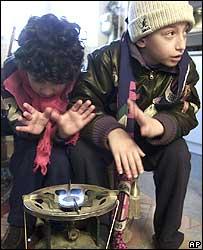 Children warming their hands on a gas cooker