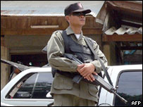 A Thai security officer stands guard in front of a house following a shooting incident in which a teacher was injured, southern Narathiwat province, 28 June 2005.