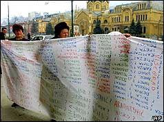 Srebrenica women hold a banner with the names of missing people