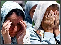 Bosnian Muslim women cry at ceremony marking earlier Srebrenica anniversary