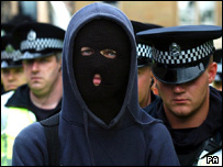 Masked protester with police officers