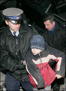Police officers evacuate a schoolboy from the site of the accident