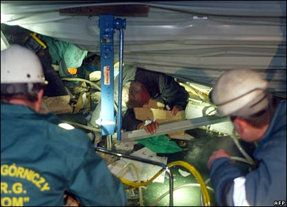Rescuers try to pull out a trapped man