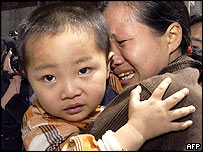 A woman cries as she is reunited with her son, one of the children rescued from a group of human traffickers in Zhengzhou, central China's Henan province 06 May 2005.