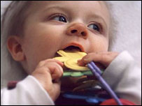 Baby with rattle in cot