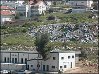 Rubbish dump of a Jewish settlement (pictured in background) located next to a Palestinian school in the West Bank