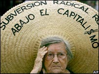 An activist wearing a hat which read's 'radical subversion, no to capitalism'