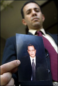 Unidentified man shows picture of  Ihab al-Sherif in Cairo