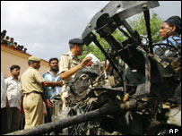 Police examine the wreckage of a jeep used in the attack