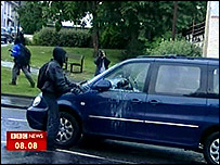 Protester smashing car window in Stirling