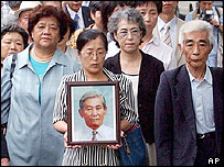 A group of Japanese war orphan plaintiffs, carrying the portrait of a dead plaintiff, with their supporters and lawyers, head to Osaka district court in Osaka, western Japan, Wednesday, July 6, 2005