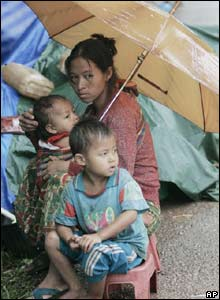 Hmong hill tribes take shelter along the road to Ban Huay Nam Khao village in Phetchabun province, north-eastern Thailand