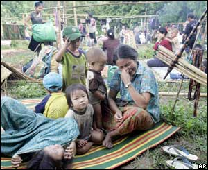 A Hmong refugee cries after being forced to abandon her house at Ban Huay Nam Khao village