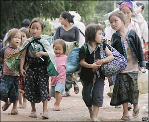 Young Hmong make their way through Ban Huay Nam Khao village after being forced to abandon their bamboo houses in Phetchabun province