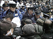 Homeless people and supporters, foreground, jostle with security officers as they protest against the removal of their tents from a park in Osaka, western Japan, Monday, Jan. 30, 2006.