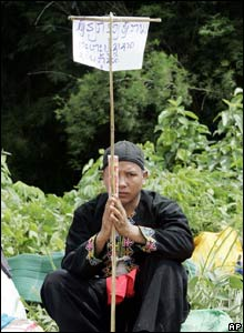A Hmong refugee holds a banner begging for help from the UN