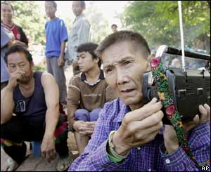Hmong people listen to the news outside their makeshift shelters at Ban Huay Nam Khao village in Phetchabun province