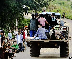 A tractor carrying Thai farmers drives past Hmong taking shelter along the road to Ban Huay Nam Khao village