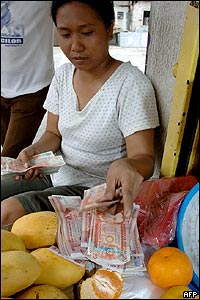 A fruit seller counting peso notes in Manila