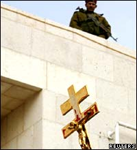 A Palestinian policeman watches a Christian procession in Bethlehem