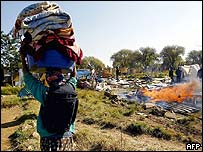 Woman carrying clothes at Angolan camp near Johannesburg in South Africa