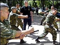 Kyrgyz police officers train with a French gendarme-instructor in Bishkek 20 June 2005.