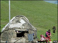 A Kyrgyz woman cooks food outside a traditional Kyrgyz dwelling - a yurt by a pass in Kuzart some 300 kilometres from Bishkek, 05 July 2005.