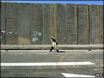 A Palestinian man walks past the barrier in the town of A-Ram near Jerusalem
