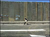 A Palestinian man walks past the barrier in the town of al-Ram near Jerusalem