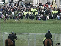 Demonstrators break through a police line and enter a field near the security perimeter surrounding the Gleneagles Hotel