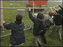 Protesters tear down a security fence near the site of the G8 summit