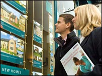 Buyers looking for home in estate agent's window