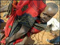 Mother carries boy on her back in northern Kenya