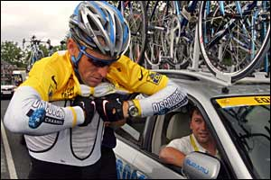 Armstrong stops to pull on the yellow jersey