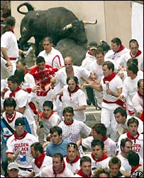 Runners try to outpace a bull in Pamplona, 7 July 2005