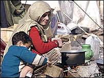 A quake survivor makes food outside her tent in Muzaffarabad