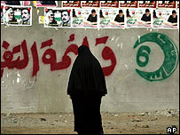 A veiled Palestinian woman walks by a wall painted with the symbol of Hamas