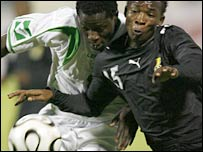 Ghana's John Pantsil (r) challenges Benjani for the ball