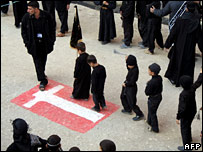 Iraqi children walk over a Danish flag drawn on the ground