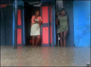 Women shelter themselves from the rain in Les Cayes, Haiti