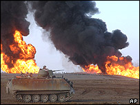 A US military vehicle passes a burning oil pipeline near Fallujah, Iraq.