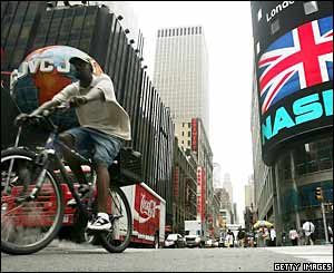 A cyclist passes the Nasdaq Marketsite in Times Square displaying a message of solidarity for London