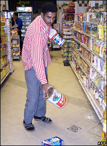An employee removes Danish goods from the shelves of an Egyptian supermarket