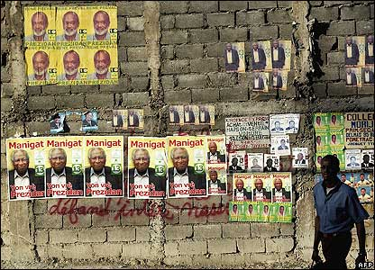 A Haitian man walks past election posters in Port-au-Prince