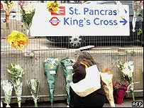 A woman leaves flowers at King's Cross